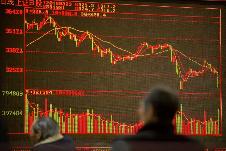 Chinese investors monitor stock prices at a brokerage house in Beijing, Friday, March 23, 2018. Fears of a trade war roiled financial markets and sent the dollar wobbling Friday after Beijing retaliated against the Trump administration's tariff hikes by threatening import duties on U.S. goods. (AP Photo/Mark Schiefelbein) Photo: Mark Schiefelbein / Copyright 2018 The Associated Press. All rights reserved.
