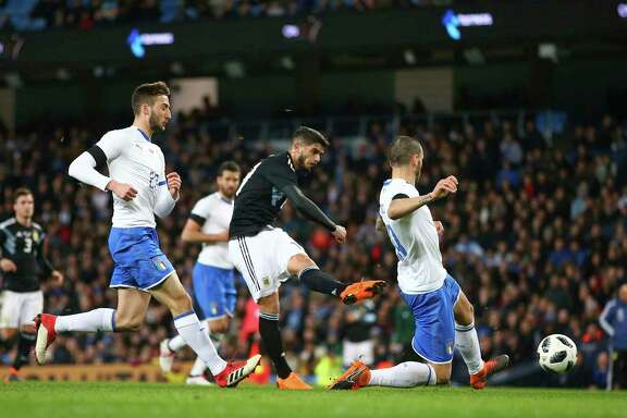 Argentina's Ever Banega, center, scores his side's first goal during the international friendly soccer match between Argentina and Italy at the Etihad Stadium in Manchester, England, Friday, March 23, 2018. (AP Photo/Dave Thompson)