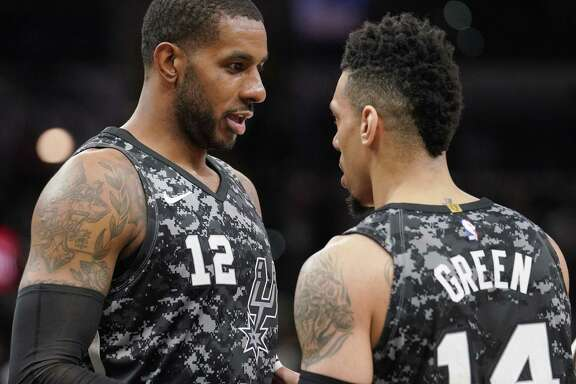 San Antonio Spurs' LaMarcus Aldridge (12) and Danny Green talk during the first half of the team's NBA basketball game against the Washington Wizards, Wednesday, March 21, 2018, in San Antonio.