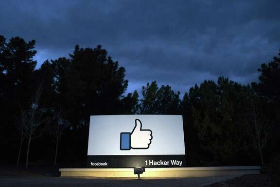 "A lit sign is seen at the entrance to Facebook's corporate headquarters location in Menlo Park, California on March 21, 2018. Facebook chief Mark Zuckerberg vowed on March 21 to ""step up"" to fix problems at the social media giant, as it fights a snowballing scandal over the hijacking of personal data from millions of its users."