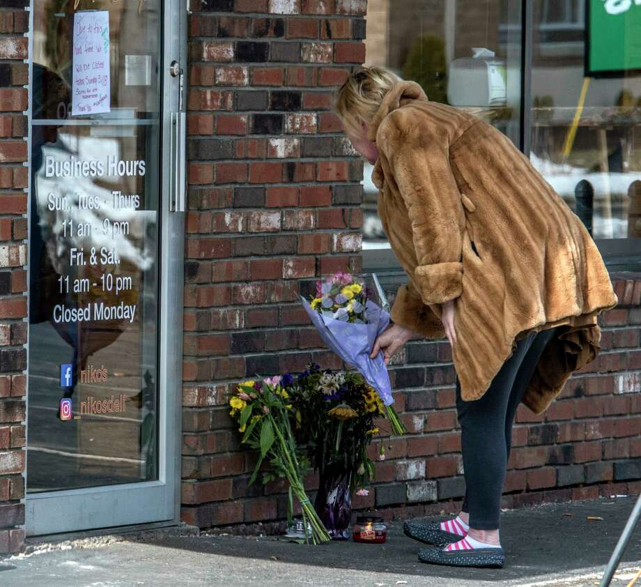 A person drops a bouquet at Niko's Restaurant Tuesday March 20, 2018 in Colonie, N.Y. adding to a makeshift memorial for Niko DiNovo who passed away yesterday from injuries from a fiery crash in 2016. (Skip Dickstein/Times Union) Photo: SKIP DICKSTEIN / 20043260A