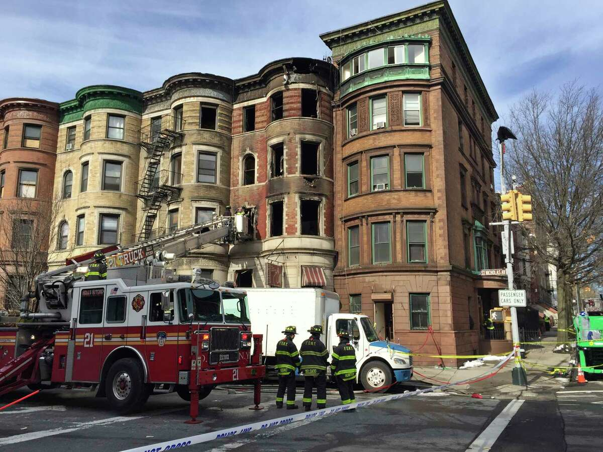 """Firefighters work at the scene of a fire Friday, March 23, 2018 that began overnight in the Harlem neighborhood of New York. Firefighter Michael R. Davidson of Engine Company 69, died after he became separated from his unit as they battled the fierce, smoky blaze that broke out in the basement of a former Harlem jazz club being used as a film set for """"Motherless Brooklyn,"""" directed by Edward Norton. (AP Photo/Jennifer Peltz)"""