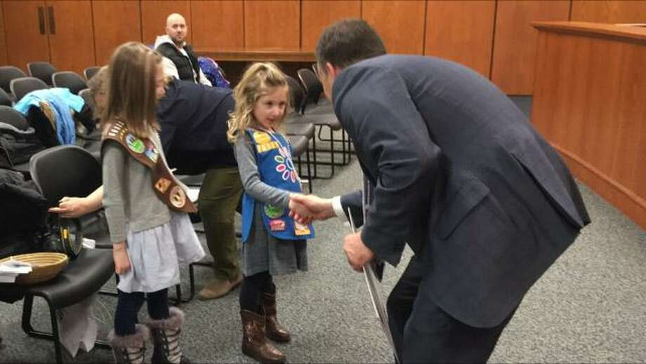 First Selectman Peter Tesei greets and congratulates Greenwich Girl Scouts Ryle Shanhan and Isabelle Shanahan as part of a special Town Hall ceremony as he declared March 12 as Girl Scout Day in town. Photo: Contributed Photo