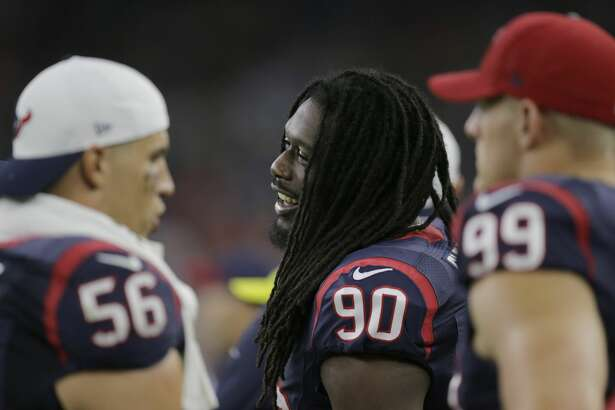Houston Texans' Jadeveon Clowney  (90) with teammates Brian Cushing (56) and J.J. Watt (99) on the sideline during the first half of an NFL preseason football game against the Denver Broncos, Saturday, Aug. 22, 2015, in Houston. (AP Photo/Patric Schneider)
