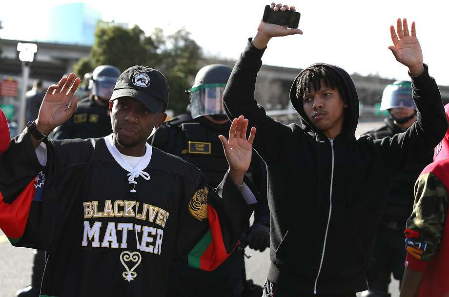 Black Lives Matter protesters stand with their hands up in front of California Highway Patrol officers as they block an entrance to Interstate 5 during a demonstration on March 23, 2018 in Sacramento.The California Department of Justice will review policing practices in the Sacramento Police Department after the fatal police shooting of Stephen Clark. Photo: Justin Sullivan, Getty Images