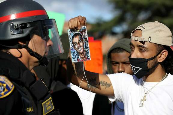 SACRAMENTO, CA - MARCH 23:  A Black Lives Matter protester holds a photo of Stephon Clark in front of a California Highway Patrol officer as they block an entrance to Interstate 5 during a demonstration on March 23, 2018 in Sacramento, California.  For a second day, dozens of protesters marched through Sacramento to demonstraate against the Sacramento police department after two officers shot and killed Stephon Clark, an unarmed black man, in the backyard of his grandmother's house following a foot pursuit on Sunday evening.  (Photo by Justin Sullivan/Getty Images)
