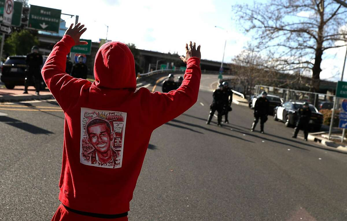 SACRAMENTO, CA - MARCH 23: A Black Lives Matter protester wears a sweatshirt with an image of Stephon Clark as he approaches California Highway Patrol officers that are blocking an entrance to Interstate 5 during a demonstration on March 23, 2018 in Sacramento, California. For a second day, dozens of protesters marched through Sacramento to demonstraate against the Sacramento police department after two officers shot and killed Stephon Clark, an unarmed black man, in the backyard of his grandmother's house following a foot pursuit on Sunday evening. (Photo by Justin Sullivan/Getty Images)