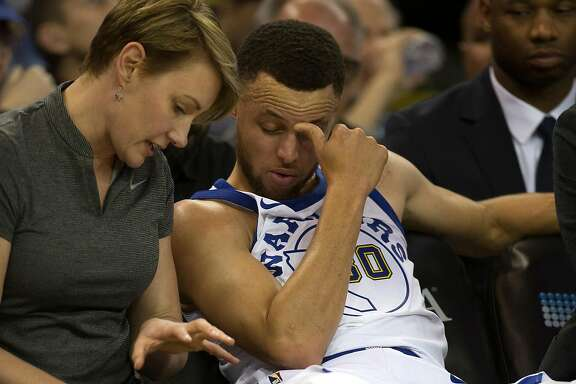 Golden State Warriors trainer Chelsea Lane, left, confers with guard Stephen Curry after he sustained an injury during the third quarter of an NBA basketball game,  Friday, March 23, 2018 in Oakland, Calif.