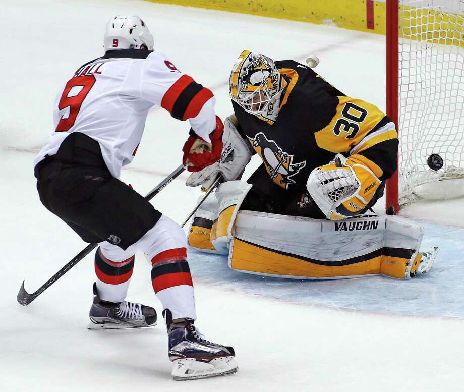 New Jersey Devils' Taylor Hall (9) puts the puck behind Pittsburgh Penguins goaltender Matt Murray (30) for an overtime goal during an NHL hockey game in Pittsburgh, Friday, March 23, 2018. The Devils won 4-3. (AP Photo/Gene J. Puskar) Photo: Gene J. Puskar / Copyright 2018 The Associated Press. All rights reserved.