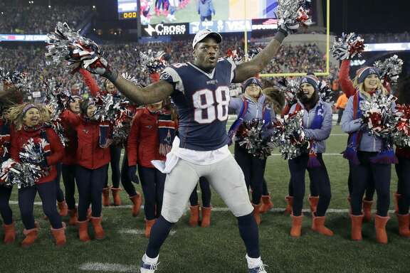 FILE - In this Jan. 22, 2017 file photo, New England Patriots tight end Martellus Bennett celebrates with cheerleaders after the AFC championship NFL football game against the Pittsburgh Steelers in Foxborough, Mass.  Bennett has filled Rob Gronkowski's shoes in more ways than one. (AP Photo/Charles Krupa)