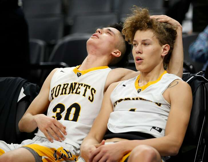 Alameda's Ryan Cibull (30) and Benno Zecic (1) react on the bench after losing to Crossroads in the Division II boys 2018 CIF Basketball State Championships at Golden 1 Center on Friday, March 23, 2018, in Sacramento, Calif.
