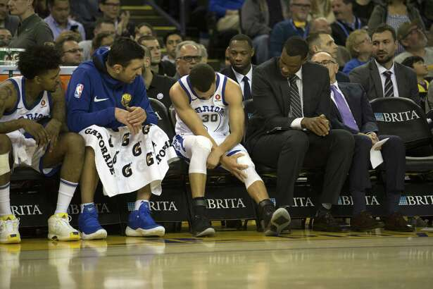 Golden State Warriors center Stephen Curry (30) sits on the bench after injuring his leg during the third quarter of an NBA basketball game,  Friday, March 23, 2018 in Oakland, Calif.