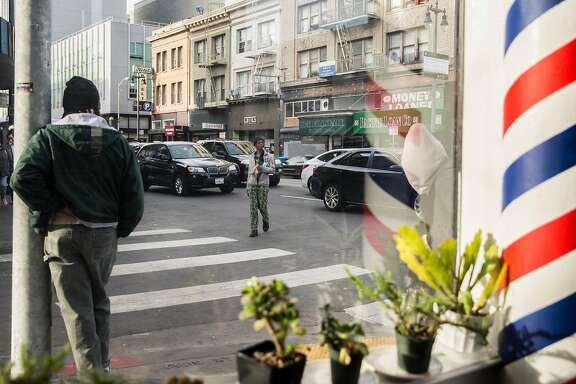 People walk through traffic outside Pentacle Coffee Tuesday, March 6, 2018 along Sixth Street in San Francisco, Calif.
