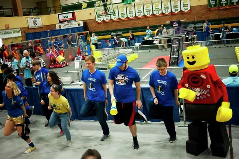 Rogue Robots alumni Isaac Davis, dressed as the team's mascot in a Lego minifigure costume, dances to 'Cotton-Eye Joe' alongside Midland High students during the FIRST Robotics District Competition on Friday at H. H. Dow High School. (Katy Kildee/kkildee@mdn.net)