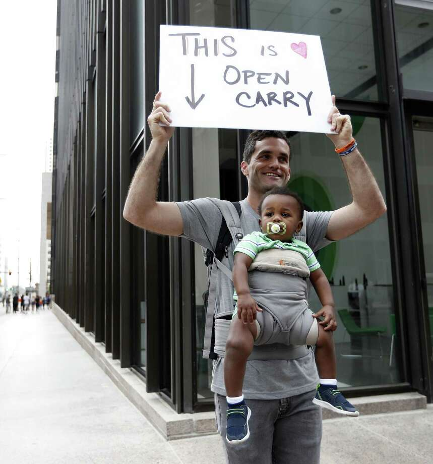 "Trip Galleher holds a sign reading ""This is Open Carry"" while holding one-year-old Wendell, during the March for Our Lives protest and march starting at Tranquility Park, Saturday, March 24, 2018, in Houston. After the recent mass shooting at Stoneman Douglas, students of the school have organized a nationwide protest including Houston, TX to plea for a strengthening of gun laws.  ( Karen Warren / Houston Chronicle ) Photo: Karen Warren,  Staff / Houston Chronicle / © 2018 Houston Chronicle"