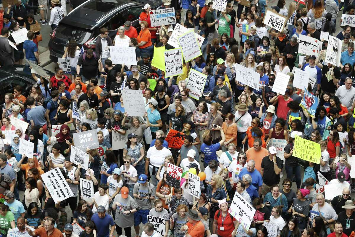 The protesters stand outside of Senator Ted Cruz's office during the March for Our Lives protest and march starting at Tranquility Park, Saturday, March 24, 2018, in Houston. After the recent mass shooting at Stoneman Douglas, students of the school have organized a nationwide protest including Houston, TX to plea for a strengthening of gun laws. ( Karen Warren / Houston Chronicle )