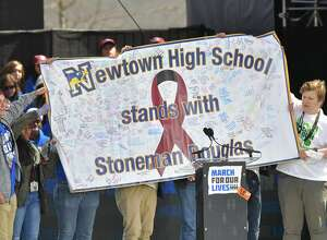 Students from Newton High School hold up a banner for Marjory Stoneman Douglas High School  during the March for Our Lives Rally in Washington, DC on March 24, 2018.  Galvanized by a massacre at a Florida high school, hundreds of thousands of Americans are expected to take to the streets in cities across the United States on Saturday in the biggest protest for gun control in a generation. / AFP PHOTO / MANDEL NGAN        (Photo credit should read MANDEL NGAN/AFP/Getty Images)