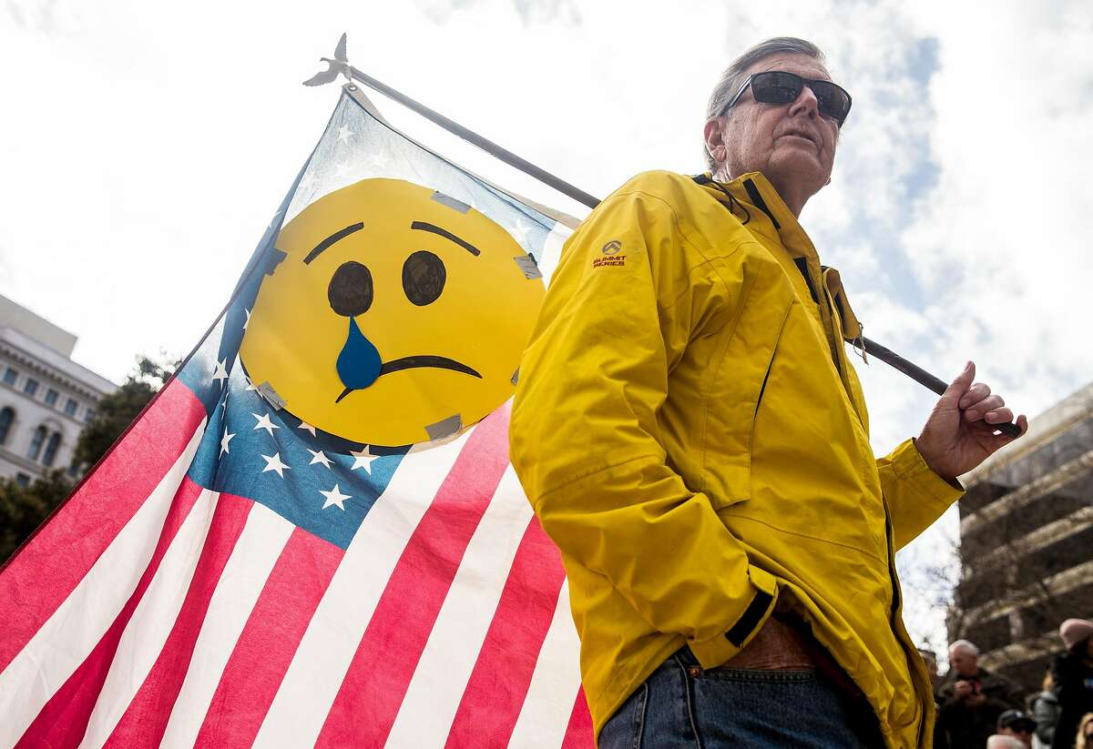 Ed Moffatt of Orinda carries an American Flag with a crying face taped on it during the March For Our Lives rally held in support of gun control and youth activism Saturday, March 24, 2018 at Frank Ogawa Plaza in Oakland, Calif.