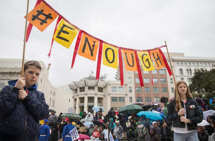 """Oscar Blair, 13, and Betty Blair, 11, of Oakland carry a homemade sign that reads """"Enough"""" during the March For Our Lives rally held in support of gun control and youth activism Saturday, March 24, 2018 at Frank Ogawa Plaza in Oakland, Calif."""