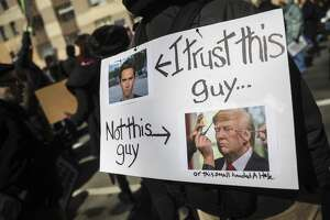 A protestor holds a sign featuring student activist David Hogg and President Donald Trump during the March For Our Lives, March 24, 2018 in New York City.