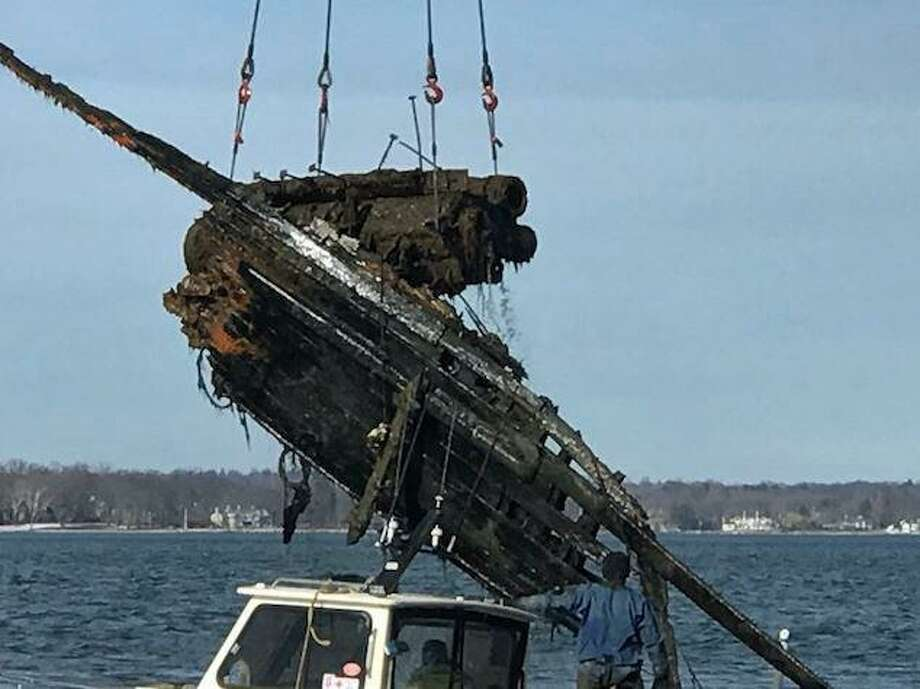 A salvage crew removes a two-ton, steel engine block that has created a hazard off Great Captain's Island since 1954. Photo: Contributed Photo