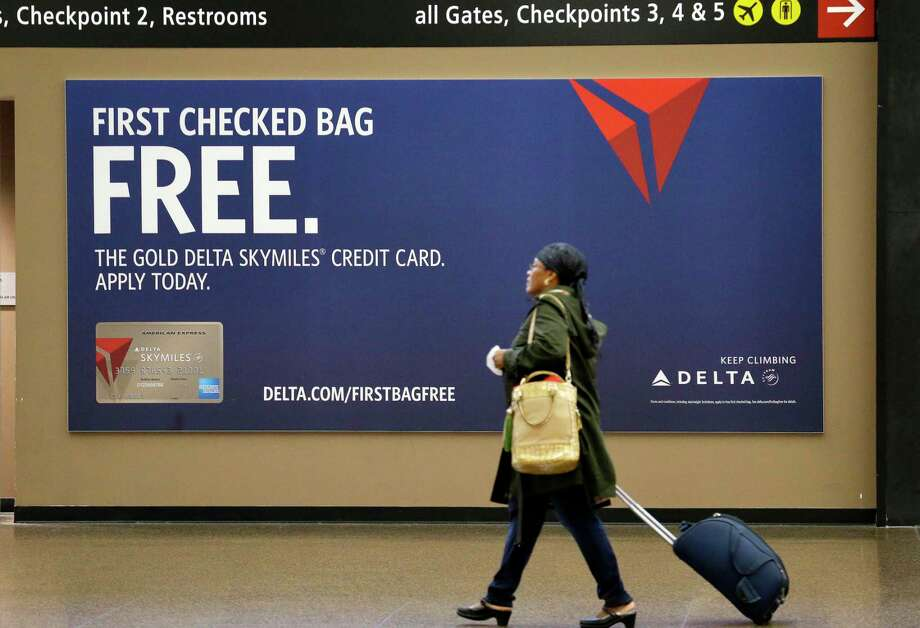 FILE - In this March 24, 2015, file photo, a traveler walks past a sign advertising a Delta Air Lines credit card at Seattle-Tacoma International Airport in SeaTac, Wash. Airline credit cards and premium travel credit cards typically charge annual fees, but you can offset that cost if the card offers free checked bags or travel credits. (AP Photo/Elaine Thompson, File) Photo: Elaine Thompson / Copyright 2017 The Associated Press. All rights reserved.