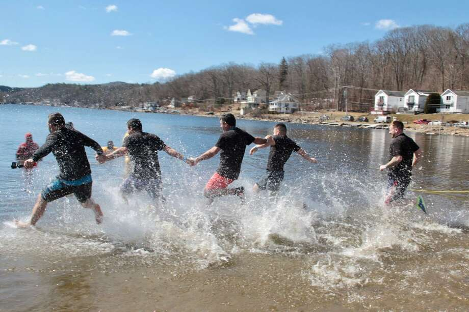 Participants of the annual Penguin Plunge run into the waters at Highland Lake in Winsted on Saturday, March 24, 2018. Photo: Anita Garnett /