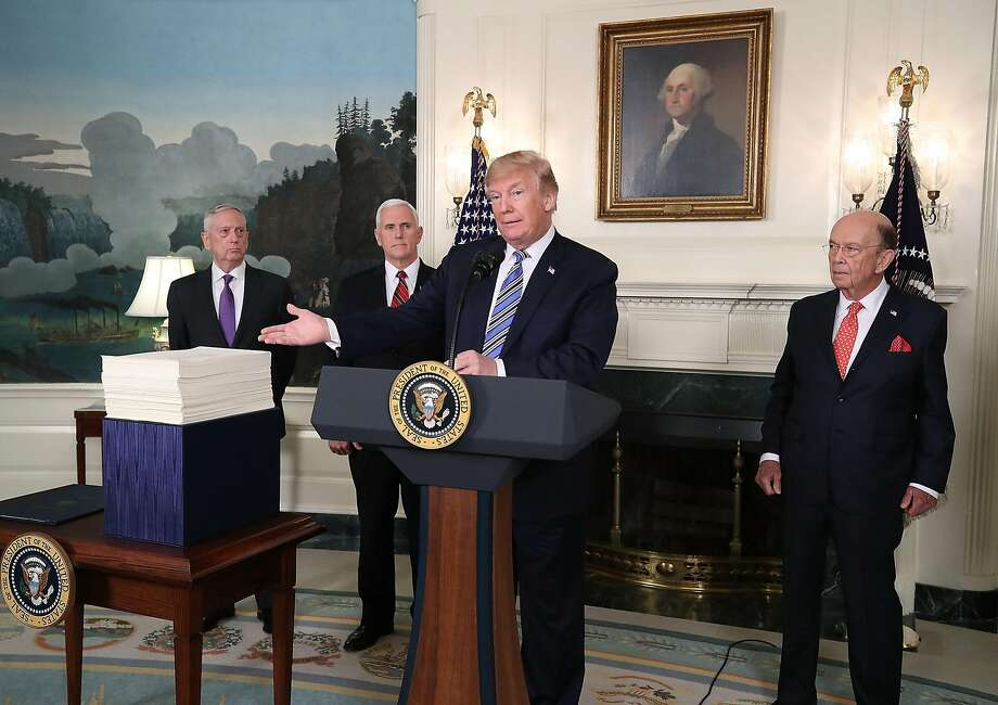 Flanked by Defense Secretary Jim Mattis (left), Vice President Mike Pence and Commerce Secretary Wilbur Ross, President Trump discusses the $1.3 trillion spending bill he signed. Photo: Mark Wilson, Getty Images