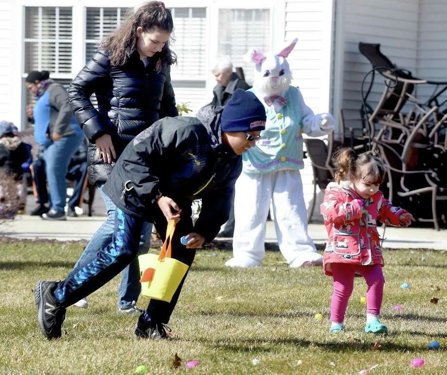 Maxwell Bradshaw (left), 10, of Hamden and Frankie Tomanelli (right), 2, of Milford search for candy during an Easter egg hunt on the lawn of the Atria Larson Place in Hamden on March 24, 2018.  At left is Frankie's mother, Hope. Photo: Arnold Gold / Hearst Connecticut Media / New Haven Register