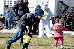 Maxwell Bradshaw (left), 10, of Hamden and Frankie Tomanelli (right), 2, of Milford search for candy during an Easter egg hunt on the lawn of the Atria Larson Place in Hamden on March 24, 2018.  At left is Frankie's mother, Hope.