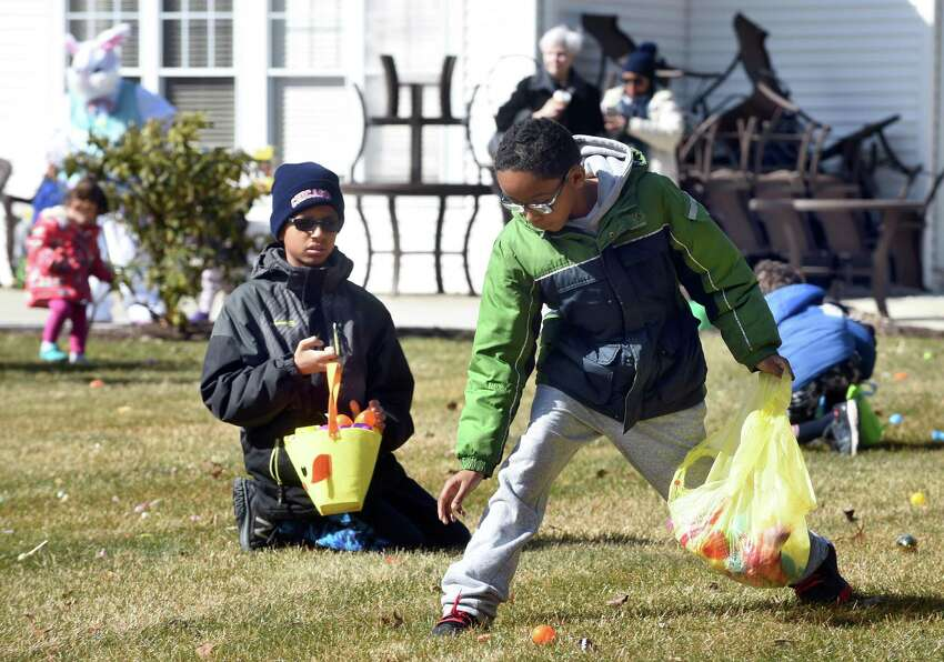 Maxwell Bradshaw (left), 10, and Donnell Edwards (right), 10, of Hamden search for candy during an Easter egg hunt on the lawn of the Atria Larson Place in Hamden on March 24, 2018.