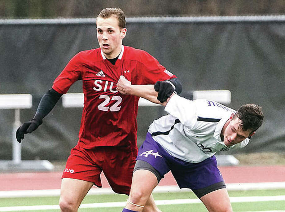 SIUE's Victor Agular (22) tries to shake free from the grasp of Evansville's Zac Blaydes during spring exhibition soccer action Saturday at Korte Stadium. SIUE won 3-0. Photo: Nathan Woodside | For The Telegraph