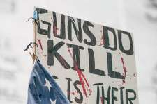"""An American flag hangs on a sign with painted blood during the """"March for Our Lives"""" demonstration on Saturday, March 24, 2018."""