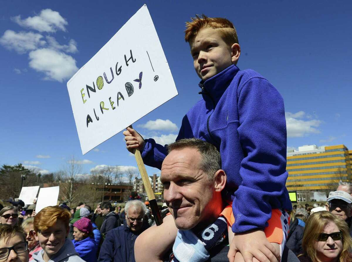 Rudy Hugh-Jones, 8, of Cos Cob sits on the shoulders of his father, Alex during the rally.