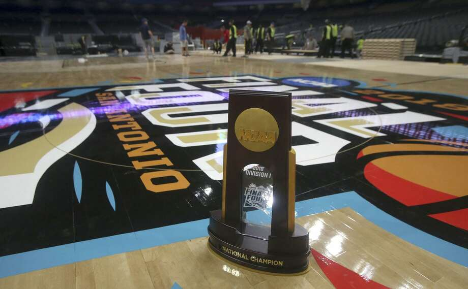 A Final Four trophy is on the floor while the floor for the official court of the 2018 NCAA Men's Final Four is installed Friday March 23, 2018 in the Alamodome in San Antonio, Texas. Connor Sports is the official court provider of the NCAA since 2006. The 2018 Men's Final Four official court is a trademarked custom built floor called QuickLock and is manufactured from northern hard maple timber from forests in Michigan. The court is 70 feet by 140 feet and is made by using 397 4-foot by 7-foot panels each weighing 188 pounds. Photo: John Davenport, STAFF / San Antonio Express-News / ©John Davenport/San Antonio Express-News