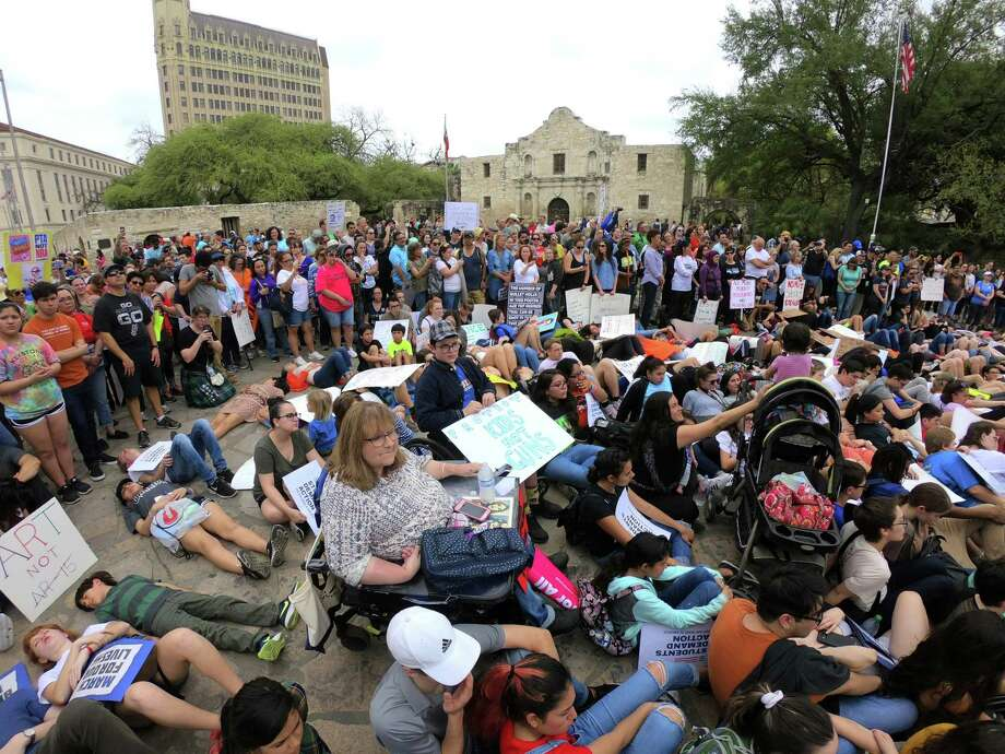 Students recline and sit in front of the Alamo in remembrance of students killed in school shootings during the March for Our Lives San Antonio on Saturday. The event was one of many such marches held across the nation, prompted by the school shootings at Stoneman Douglas High School in Parkland, Fla. Photo: Billy Calzada /San Antonio Express-News / San Antonio Express-News