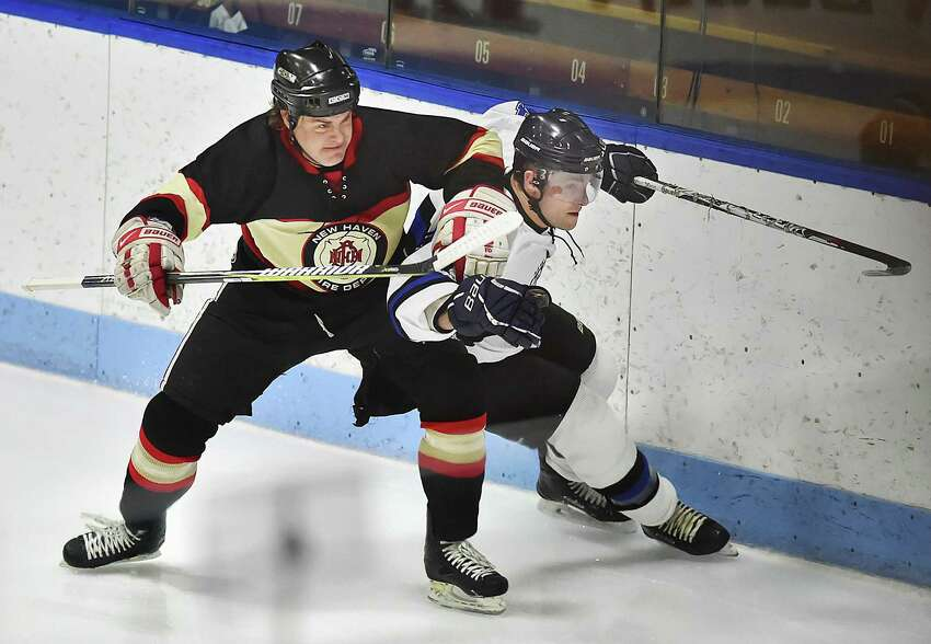 New Haven Fire Department's John Twohill races for a loose puck against New Haven Police Department's Tom Marchitto in the 22 annual City of New Haven Chief's Cup, on Saturday, at Ingalls Rink.