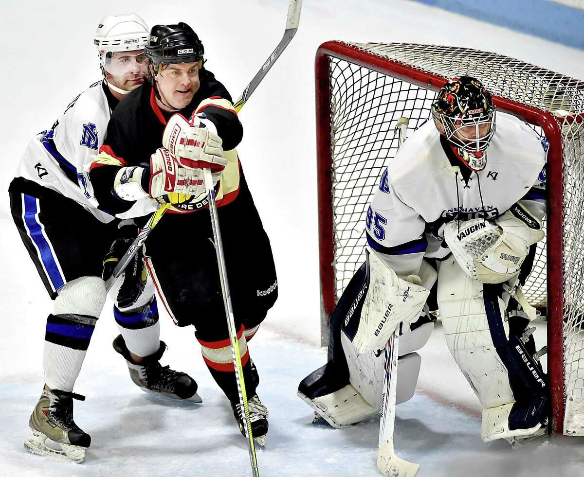 New Haven Police Department goalie Justin Eddy keeps an eye on the puck while New Haven Fire Department's John Twohill and NHPD's Steve Torquati battle for position in the 22 annual City of New Haven Chief's Cup, Saturday, March 24, 2018, at Ingalls Rink. Final score, 7-7, in regulation, the NHPD won, 8-7, in overtime.