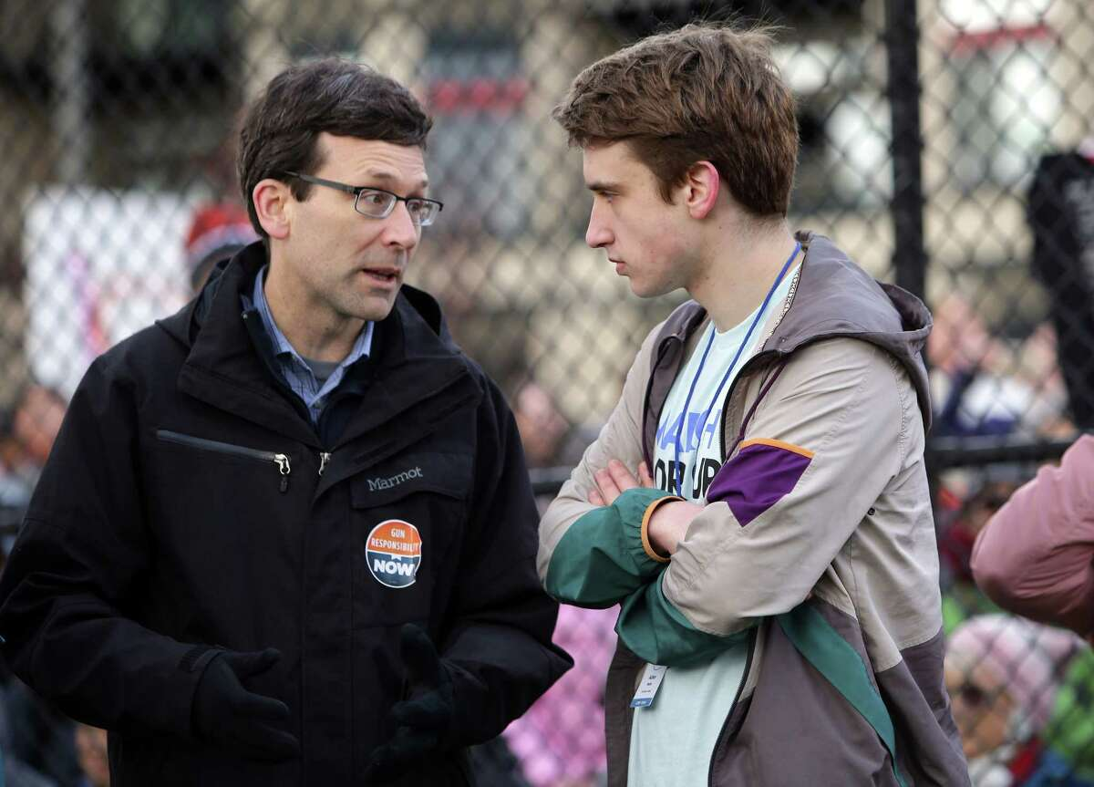 Washington Attorney General Bob Ferguson speaks with march Shorecrest High Schoo student Asher Maria during the