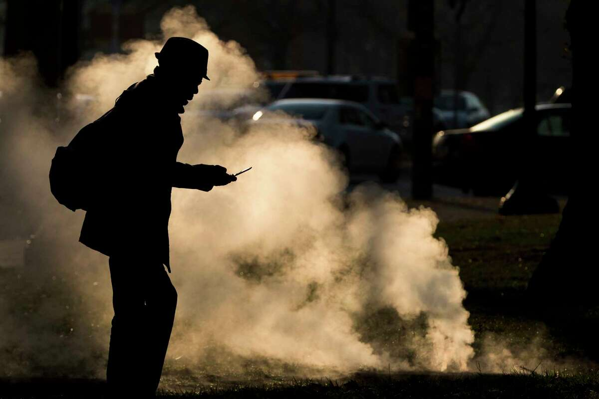 FILE - In this Nov. 30, 2012 file photo, a pedestrian looks at his phone near steam vented from a grate near the Philadelphia Museum of Art on a cold morning in Philadelphia. Every time a person shops online or at a store, loyalty cards linked to phone numbers or email addresses can be linked to other databases that may have location data, home addresses and more. Voting records, job history, credit scores (remember the Equifax hack?) are constantly mixed, matched and traded by companies in ways regulators haven?'t caught up with. (AP Photo/Matt Rourke, File)