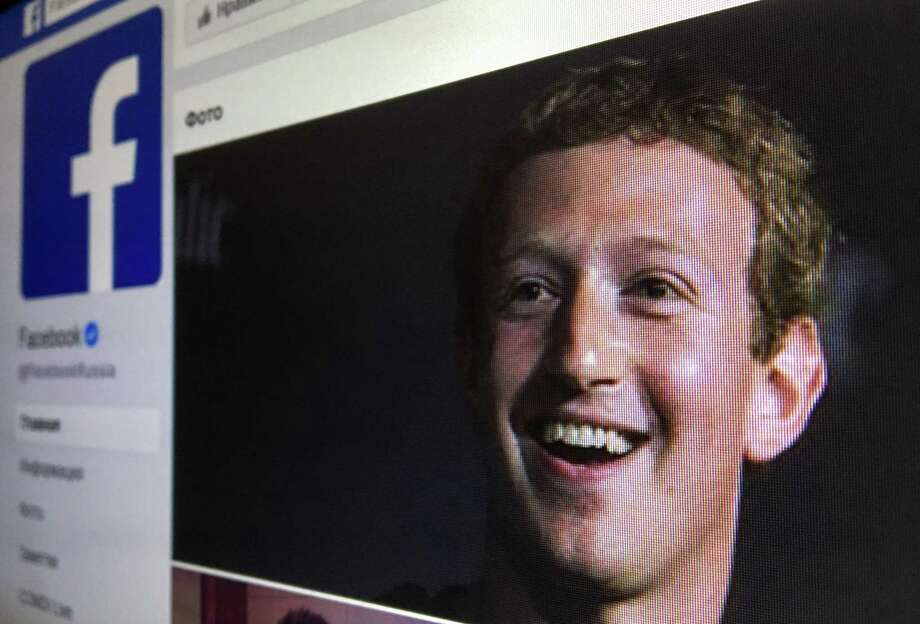 A picture taken in Moscow on March 22, 2018 shows an illustration picture of the Russian language version of Facebook about page featuring the face of founder and CEO Mark Zuckerberg.