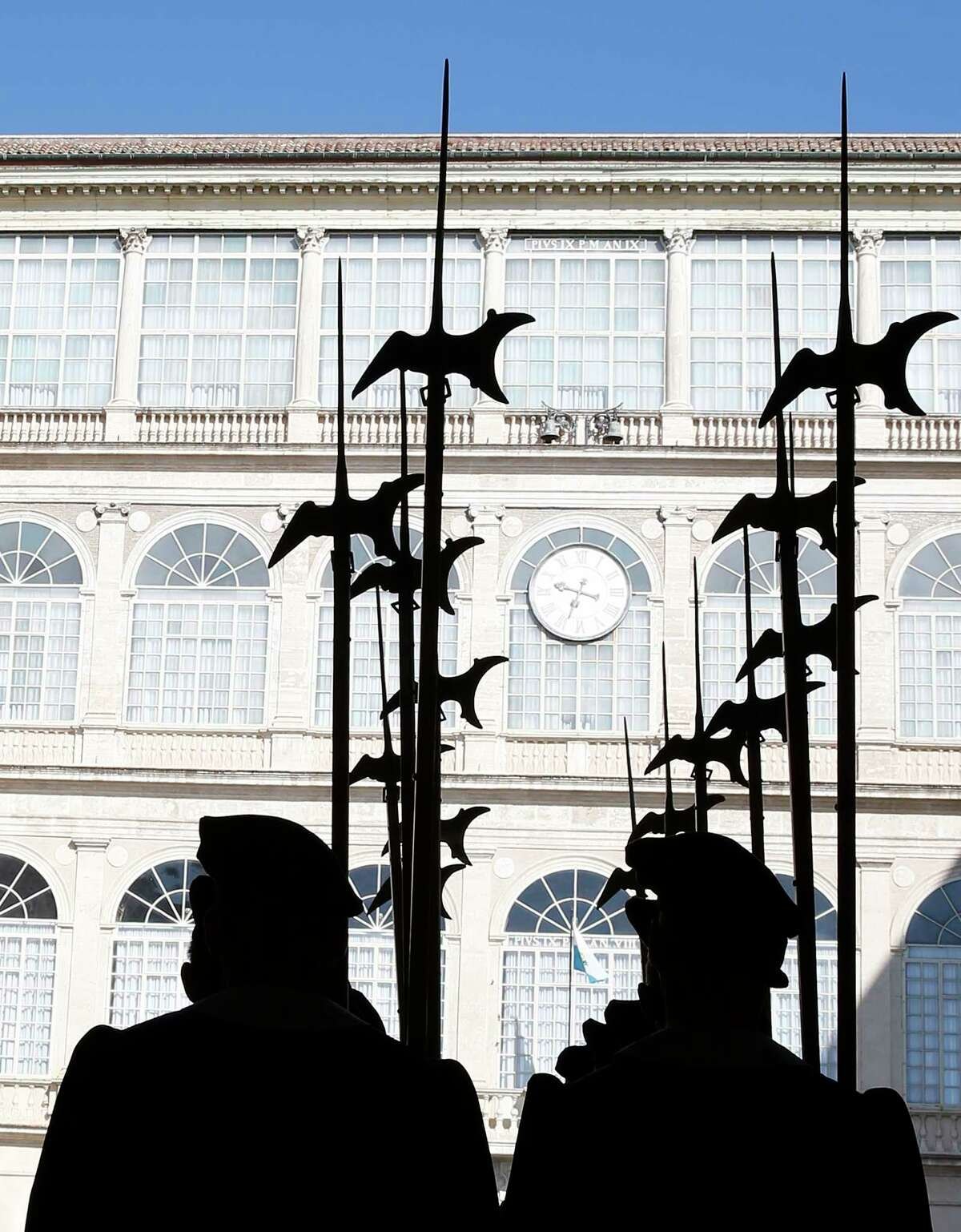 Vatican Swiss guards are silhouetted in the Vatican's courtyard ahead of a private audience between Pope Francis and Captains Regent of San Marino Matteo Fiorini, and Enrico Carattoni, on the occasion of their private audience at the Vatican, Friday, March 23, 2018. (Stefano Rellandino/Pool Photo via AP)