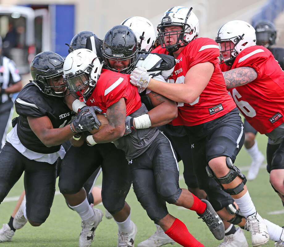Texas Tech running back Da'Leon Ward (21) is swarmed by Red Raider defenders during Saturday's spring scrimmage at Grande Communication Stadium. Wade H. Clay/Special to the Reporter-Telegram