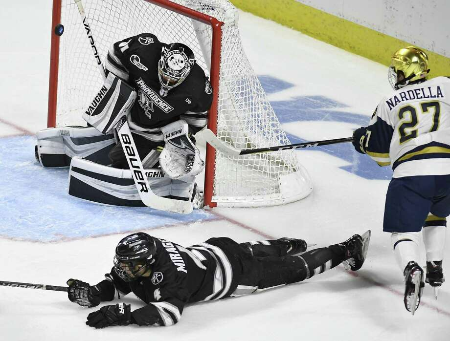 Providence goaltender Hayden Hawkey (31) deflects a shot by Notre Dame's Bobby Nardella (27) as Providence's Ben Mirageas (4) defends during the second period of an NCAA college hockey regional tournament game, Saturday, March 24, 2018, in Bridgeport, Conn. (AP Photo/Jessica Hill) Photo: Jessica Hill / Associated Press / AP2018