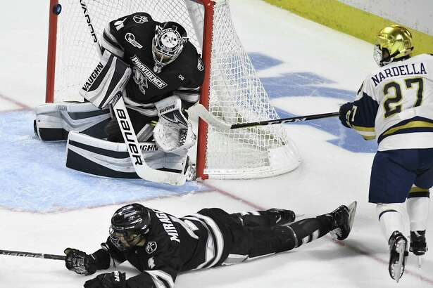 Providence goaltender Hayden Hawkey (31) deflects a shot by Notre Dame's Bobby Nardella (27) as Providence's Ben Mirageas (4) defends during the second period of an NCAA college hockey regional tournament game, Saturday, March 24, 2018, in Bridgeport, Conn. (AP Photo/Jessica Hill)