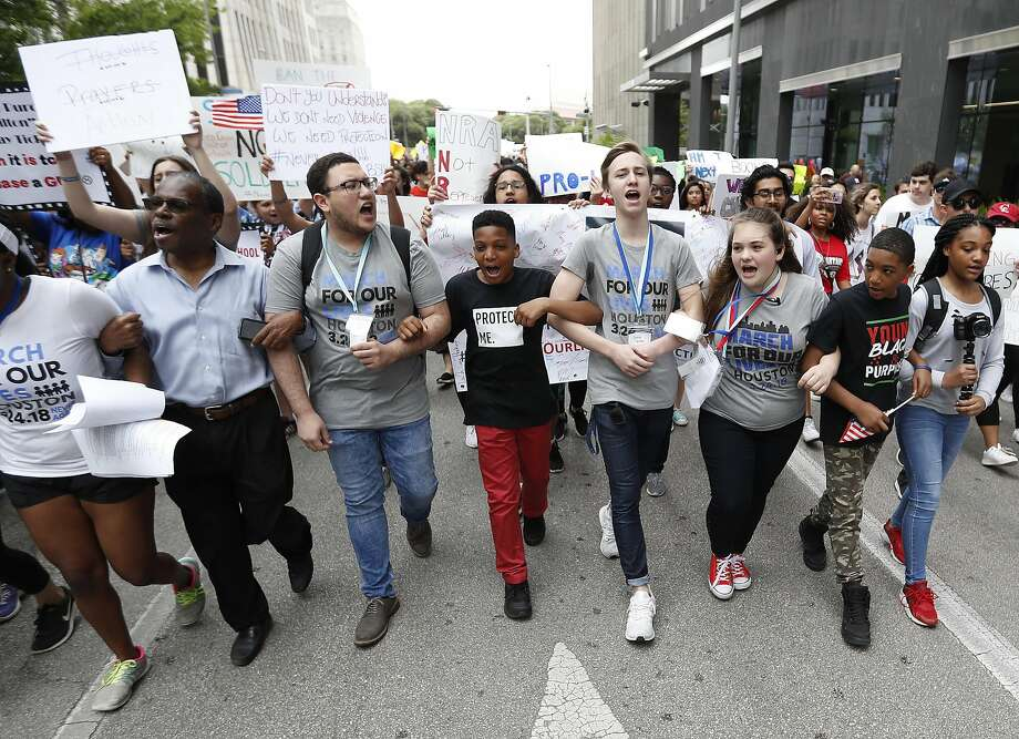 10-year-old Dezmond Floyd, of Humble, wearing red pants, joins fellow students arm-in-arm-as they began the march to Senator Ted Cruz's office during the March for Our Lives protest and march starting at Tranquility Park, Saturday, March 24, 2018, in Houston. After the recent mass shooting at Stoneman Douglas, students of the school have organized a nationwide protest including Houston, TX to plea for a strengthening of gun laws.  ( Karen Warren / Houston Chronicle ) Photo: Karen Warren, Houston Chronicle