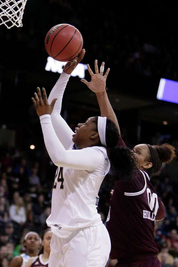 Notre Dame guard Arike Ogunbowale, left, shoots in front of Texas A&M center Khaalia Hillsman (00) during the second half in a regional semifinal at the NCAA women's college basketball tournament, Saturday, March 24, 2018, Spokane, Wash. Notre Dame won 90-84. (AP Photo/Young Kwak) Photo: Young Kwak / FR159675 AP