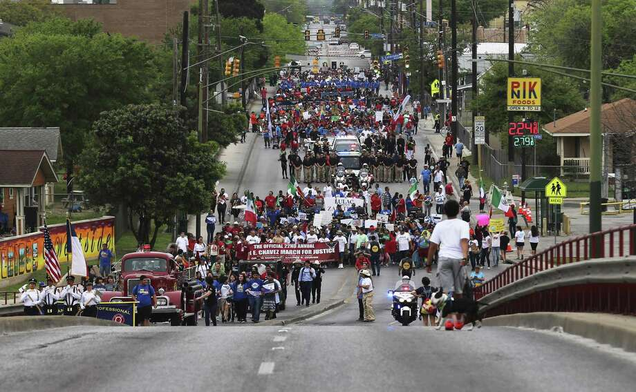 Hundreds march along Guadalupe Street and head toward the bridge as they take part in the 22nd Annual Cesar E. Chavez March for Justice on Saturday, Mar. 24, 2018. Ernest Martinez of the Cesar E. Chavez Legacy & Educational Foundation took over for his father, Jaime Martinez, who died last year after a prolonged battle with cancer. The grand marshal was Andres Chavez, the grandson of the famed American labor leader and civil rights activist. (Kin Man Hui/San Antonio Express-News) Photo: Kin Man Hui, Staff / San Antonio Express-News / ©2018 San Antonio Express-News