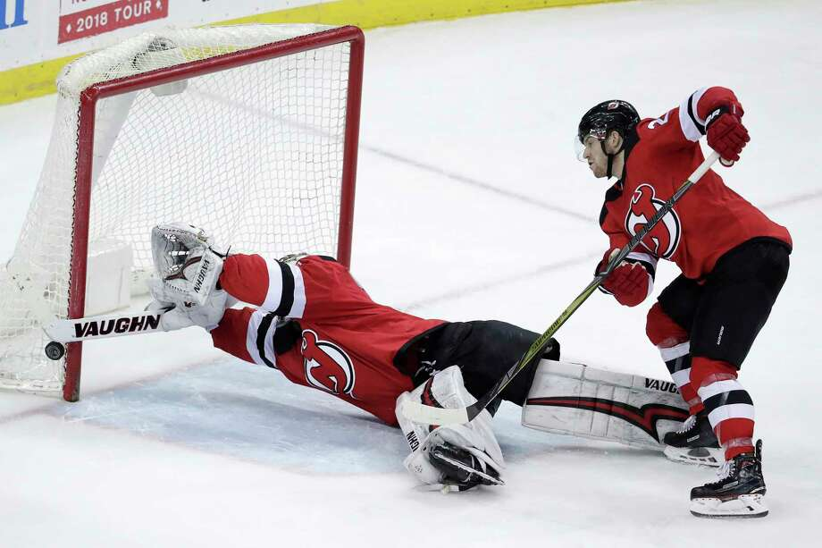 New Jersey Devils goaltender Keith Kinkaid, left, dives to make a save on a shot by Tampa Bay Lightning defenseman Ryan McDonagh, not seen, during the third period of an NHL hockey game Saturday, March 24, 2018, in Newark, N.J. Devils' Damon Severson helps defend on the play. The Devils won 2-1. (AP Photo/Julio Cortez) Photo: Julio Cortez / Copyright 2018 The Associated Press. All rights reserved.