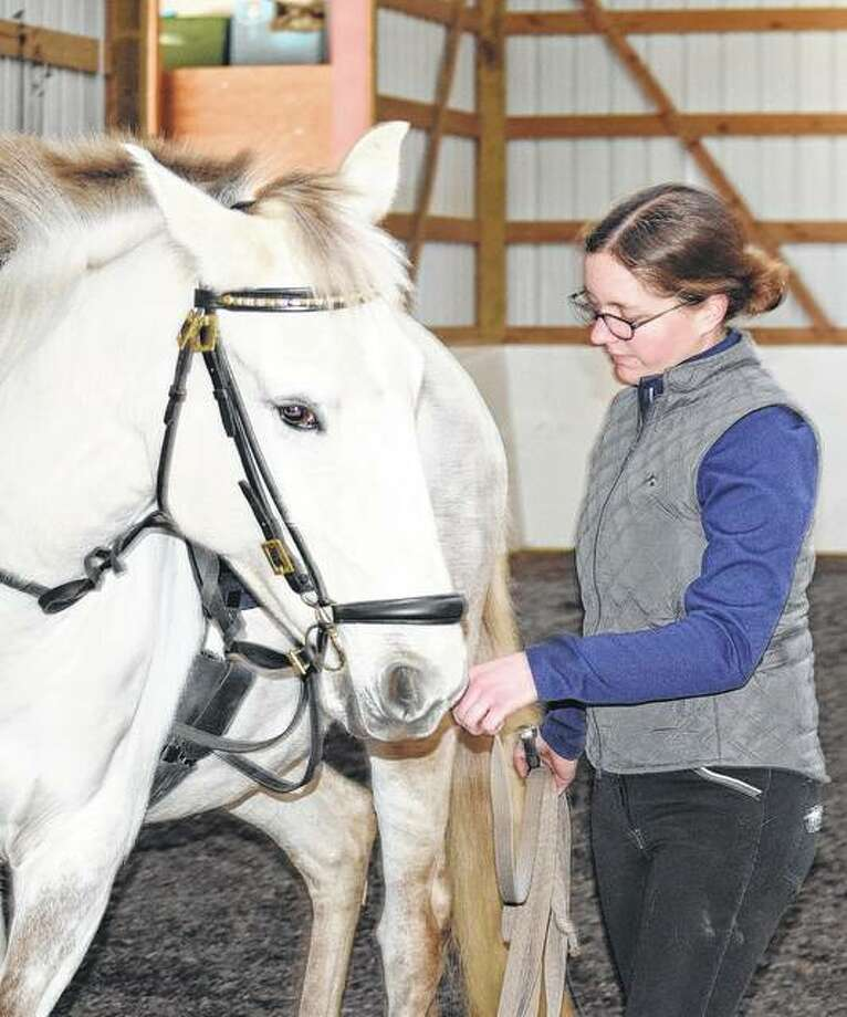 Sarah Scheerer pets Japu as a reward after performing several movements as a part of training. Photo: Samantha McDaniel-Ogletree | Journal-Courier